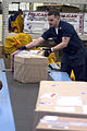 US Navy 071107-N-1251W-003 Postal Clerk 3rd Class Damon Candelarie inspects a package before it is sorted into the proper mailbox at Commander, Fleet Activities Yokosuka.jpg