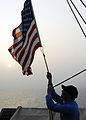 US Navy 080911-N-2183K-036 Mass Communication Specialist 2nd Class Scott A. Webb lowers a flag to half-mast at sunset aboard the amphibious assault ship USS Peleliu (LHA 5) to honor those lost during the attacks on Sept. 11, 20.jpg