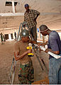 US Navy 090302-N-1655H-449 Construction Electrician 2nd Class Darius Michael, assigned to Naval Mobile Construction Battalion (NMCB) 11, works with Ghanaian Navy sailors to install a light fixture during a refurbishment project.jpg