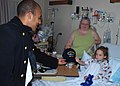 US Navy 091005-N-2893B-001 Seaman Miguel Arias, assigned to USS Constitution, gives a Navy ball cap to a patient at the Albuquerque Presbyterian Hospital during an Albuquerque Navy Week.jpg