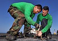 US Navy 100718-N-5650M-012 Aviation Boatswain's Mates (Equipment) 3rd Class Eliezer Arroyo and Earl Pelitaro attach chains to an arresting wire aboard the aircraft carrier USS Enterprise (CVN 65).jpg