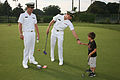 US Navy 100903-N-3271W-159 BALTIMORE (Sept. 3, 2010) Midshipman 3rd Class Pat Collins fist bump with a First Tee participant as Midshipman Ensign Robert Merkert looks on.jpg