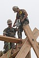 US Navy 110615-N-IL826-268 Equipment Operator 3rd Class Christopher Baca uses a heavy timber drill to help construct a 30-foot observation tower a.jpg