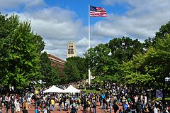 Red brick plaza, surrounded by trees with green leaves, with two white tents and an American flag flying from a flagpole in the center