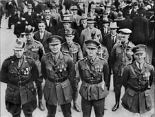 Lines of men in rows of four wearing military uniforms or suits and military medals.