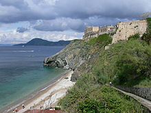Photo of a coastline with the sea, greyish cliffs, vegetation and beige buildings