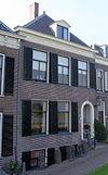 foto van Huis bestaande uit souterrain, parterre en verdieping met schilddak, waarin dakvenster met fronton