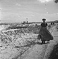 Vrouw in klederdracht loopt met as over smalspoor Achter haar werkzaamheden slu, Bestanddeelnr 900-8369.jpg