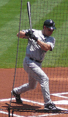 A man in a gray baseball uniform and black batting helmet stands in the batter's box twisting from the waist while holding a baseball bat