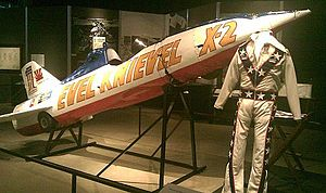 Rocket with front end tilted upwards and a flight suit in front of it.
