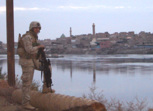 MOS 0311 - A U.S. Marine Infantryman (0311) with 1/2 Bravo Company patrols alongside the Euphrates River in Hīt, Iraq, 2005.