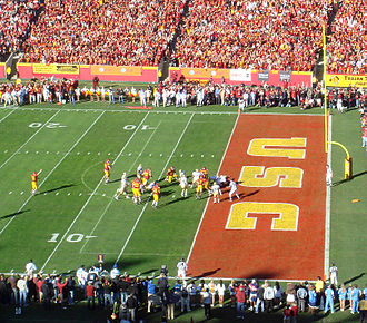 End zone - A player rushes into the red-painted end zone, scoring a touchdown during a college football game.