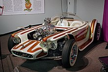 A white car with brown stripes, with open wheels and a clear bubble canopy over twin seats, and exposed, chromed engine with a blower.