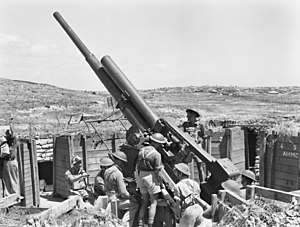 Black and white photograph of several men wearing military uniforms standing next to a large artillery gun