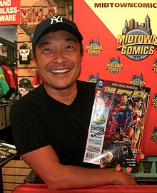 A photograph of a man wearing a black baseball cap and a black T-shirt looking at the viewer and smiling while holding a signed comic book