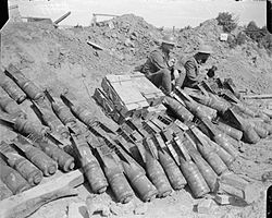 A picture taken in 1918 showing two men of the 9th Battalion, Royal Sussex Regiment sit beside a dump of 6 inch Mortar bombs.