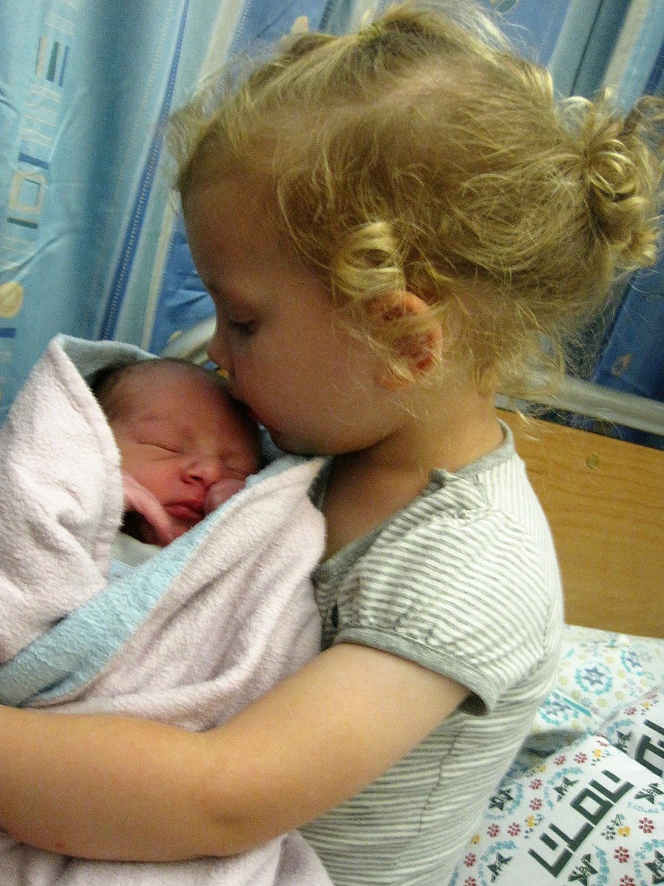 A 3-year-old embraces her brother less than a day after he was born