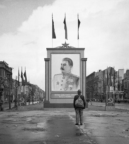 A poster of Stalin on the Unter-den-Linden in Berlin in 1945 A German civilian looks at a large poster portrait of Stalin on the Unter-den-Linden in Berlin, 3 June 1945. BU8572.jpg