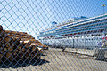 A Pile of Logs and a Cruise Ship Behind a Fence.jpg