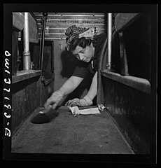 A charwoman who cleans buses sweeping the floor of a bus 8d32921v.jpg