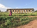 A lady walks along a foot path, adjacent to the old railway tracks in Gulu, Uganda.jpg