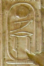 Inscription in raised hieroglyphs on a wall of light brown color