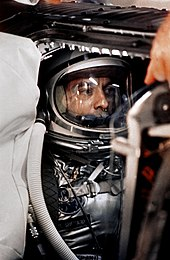 Shepard in his Mercury space suit and helmet, with tubes connected.