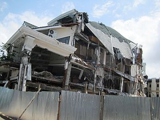 2009 Sumatra earthquakes - A destroyed house in Padang Pariaman District (left) and the 6-story Ambacang Hotel