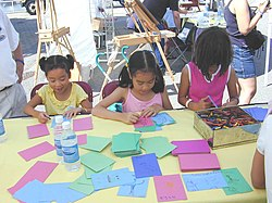 Children drawing with crayons on coloured cardstock, for the Snail Mail World Postcard Art Show.