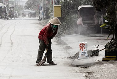 Man sweeping volcanic ash