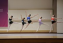 Five dancers leap on a stage. Each wears a number on her leotard.