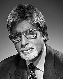 Amitabh Bachchan is looking at the camera.