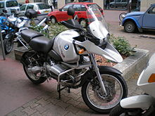 Silver BMW R1150GS parked on a city street with other cars and bikes in the background