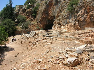 Banias - The remnants of the temple of Pan with Pan's grotto. The building with the white dome in the background is the shrine of Nabi Khadr.