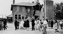 onlookers mill around, looking at the half-destroyed Bath School building