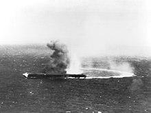 Une haute colonne de fumée s'élève au-dessus d'un porte-avions tandis qu'une large lueur est visible à sa proue. Une trainée derrière le navire indique qu'il a violemment viré sur tribord