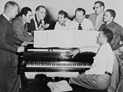 Benny Goodman (third from left) in 1952 with some of his former musicians, seated around piano left to right: Vernon Brown, George Auld, Gene Krupa, Clint Neagley, Ziggy Elman, Israel Crosby and Teddy Wilson (at piano)