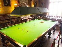 Une table de billard pleine grandeur dans une pièce bien éclairée avec des bibliothèques et une table de réunion en arrière-plan, le tout bouclé sur le côté droit dans le cadre d'une exposition de maison de campagne anglaise