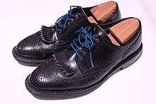 be7a65b9771bf 黒いフルブローグの革靴. 大量生産により、広く普及した現代の革靴(ビジネスシューズ ...