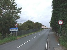 A photograph facing west along Bothkennar Road with a sign showing the entrance to the village of Carronshore.
