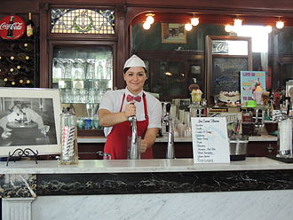 "Soda fountain - A ""soda jerk"" serving an ice cream soda in a century-old diner in Bramwell, WV (2013)"