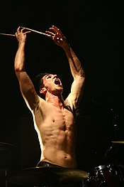 A shirtless man playing the drums