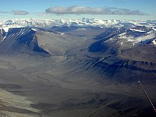 In the foreground is a landscape of dull brown mounds and undulations, behind which are snow-covered mountain peaks.