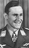 The head of a young man, shown in semi-profile. He wears a military uniform with a military decoration in shape of an iron cross displayed at the front of his shirt collar. His hair is dark and short and combed to back, his nose is long and straight, he is smiling broadly and looking to the left of the camera.