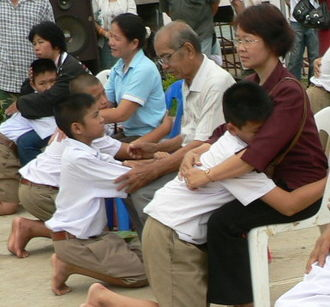 Culture of Thailand - Display of respect of the younger towards the elder is a cornerstone value in Thailand. A family during the Buddhist ceremony for young men who are to be ordained as monks.