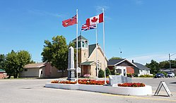Flags and the war cenotaph in Cartwright with the Cartwright United Church in the background.