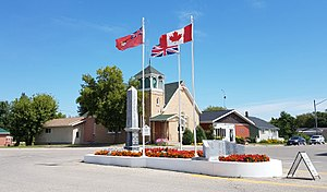Cartwright, Manitoba - Flags and the war cenotaph in Cartwright with the Cartwright United Church in the background.