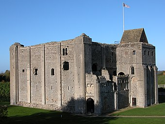 A large square castle keep of pinkish-grey stone, with a projecting entrance tower, has architectural details to its windows, mouldings and stonework.