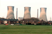 Three massive grey-taupe coloured funnels dominate the scene in which there is a flat piece of green grass in the foreground, red-brick housing in the midground, and behind them in the background the industrial funnels against a white sky. The funnels appear three or four times the size of the row of terraced properties in the midground, and stand independently of each other. Associated with them are two chimneys standing at similar height and a control building in the hazey distance.