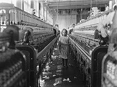 Ein Mädchen steht inmitten von Webmaschinen in einer verlassenen Fabrikhalle.